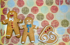 Three gingerbread cookie men on fancy background. Three gingerbread cookie men with a heart on fancy background royalty free stock image