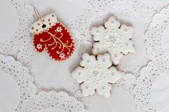 Three gingerbread cookies in the shape of red mitten and two snowflakes on a white napkin background. Top view, flat lay. Copy space. Curly Christmas Royalty Free Stock Images