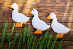 Three gingerbread cookies shaped duck with ear of wheat on a wooden background. Shallow depth of field. Royalty Free Stock Images