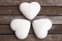 Three gingerbread hearts. Covered by white icing, on the wooden surface Stock Image