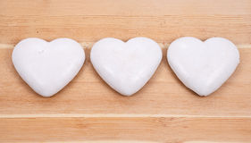 Three gingerbread hearts on wooden background. Three white gingerbread hearts on wooden background Royalty Free Stock Photo