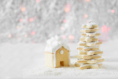 Three gingerbread houses,fir-tree and cookie men on the background of bokeh and snow Stock Photos