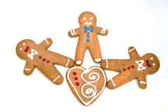 Three gingerbread men with a cookie heart isolated. On white stock images