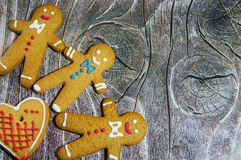 Three gingerbread men. And a heart on wood background stock photos