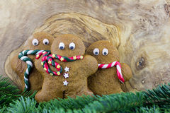 Three gingerbread men and pine branches Royalty Free Stock Images