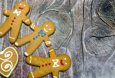 Three gingerbread men on wood. Background stock photography