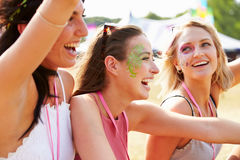 Three girl friends laughing at a music festival Royalty Free Stock Photography