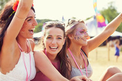 Three girl friends at a music festival, one turned to camera Royalty Free Stock Photos