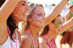Three girl friends at a music festival, side view Royalty Free Stock Image