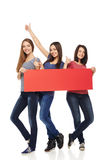 Three girl friends with red banner Stock Photos