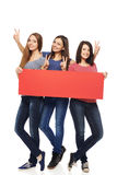 Three girl friends with red banner. Women billboard sign. Fill length of three excited women showing blank red placard and gesturing V sign, over white Stock Photography