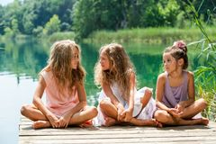 Three girl friends sitting on jetty at lake. Portrait of young female threesome having conversation on river jetty Stock Photos