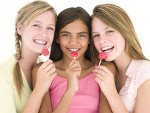 Three girl friends with suckers smiling stock photos