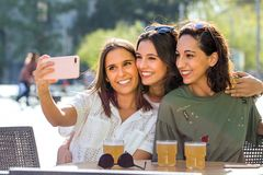 Three girl friends taking selfie photo on terrace. stock photography