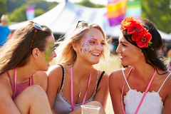 Three girl friends talking at a music festival Royalty Free Stock Image