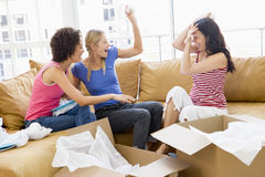 Three girl friends unpacking boxes in new home Royalty Free Stock Photo