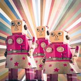 Three girl robot toys looking forward,. Toned image Stock Images