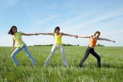 Three girlfriend in green field Stock Photos