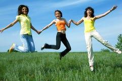 Three girlfriend jump in green field stock image