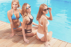Three girlfriends chilling at poolside Royalty Free Stock Images