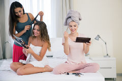 Three girlfriends doing makeup and hairstyle Stock Photos