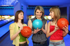 Three girlfriends hold balls for bowling stock photos