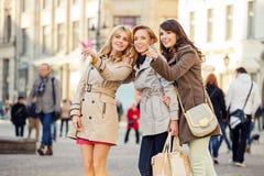 Three girlfriends indicating something interesting royalty free stock photography