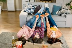 Three Girlfriends in jeans and shirts eating Pizza at home, lying on the floor and put legs on the sofa stock photos