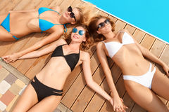 Three girlfriends lying head to another at pool Royalty Free Stock Photos