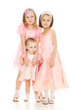 Three girlfriends in pink dresses hug Royalty Free Stock Photo
