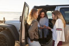 Three girlfriends planning road trip with tablet computer stock photography