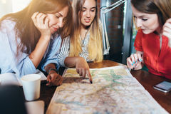 Three girlfriends planning their vacation sitting at table around map choosing the destination.  Stock Photo