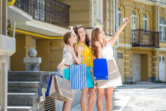 Three girlfriends posing make selfie on a cell phone. Girls hold Stock Image