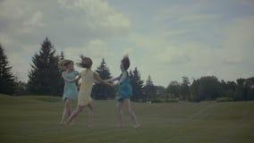 Three girlfriends round dance in summer field stock video footage