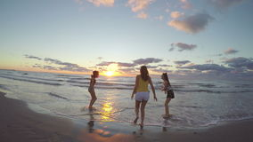 Three girlfriends running on sandy beach towards the sea and playing with their feet in the water stock video footage