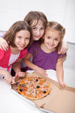 Three girlfriends sharing a pizza Stock Photo