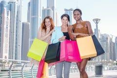 Three girlfriends shopaholic. Beautiful girl in dress holding sh Stock Image