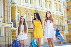 Three girlfriends shopaholics. Girls holding shopping bags and w Royalty Free Stock Images