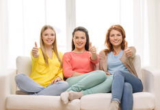 Three girlfriends showing thumbs up at home. Friendship, gesture and happiness concept - three girlfriends showing thumbs up at home Stock Image