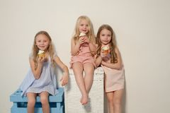 Three girlfriends sisters eat sweet lollipop candy royalty free stock photos