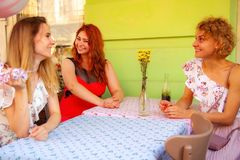 Three girlfriends are sitting in a cafe on the street and smiling. royalty free stock photo