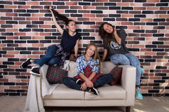 Three girlfriends sitting on the couch and smiling Stock Image