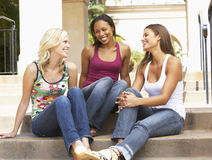 Three Girlfriends Sitting On Steps Of Building stock image