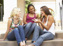 Three Girlfriends Sitting On Steps Of Building Stock Photography