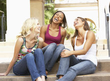 Three Girlfriends Sitting On Steps Of Building. Chatting and Laughing Royalty Free Stock Photo