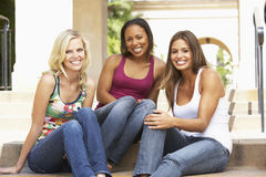 Three Girlfriends Sitting On Steps Of Building. Smiling To Camera Royalty Free Stock Image