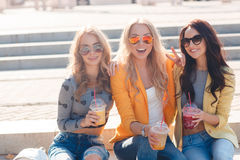 Three girlfriends sitting on steps in Park. Three beautiful young women,two blondes and a brunette sitting on the steps, drinking fruit juice and wearing sun royalty free stock photos