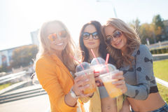 Three girlfriends sitting on steps in Park Stock Photography
