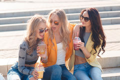 Three girlfriends sitting on steps in Park Stock Images
