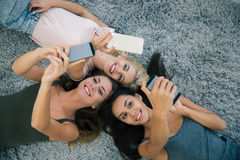 Three girlfriends using smartphones Royalty Free Stock Photos